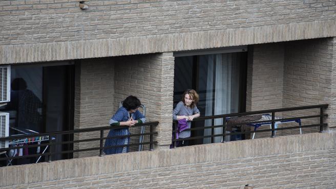 Dos mujeres conversan desde sus balcones en València.