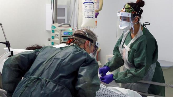 Dos enfermeras atienden a un paciente de COVID-19 en la unidad de cuidados intensivos del hospital Frimley Park, en Surrey, Reino Unido.