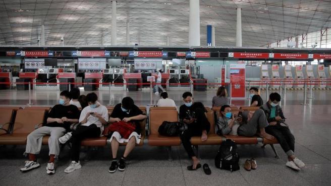 Pasajeros esperan en el aeropuerto internacional de Pekín, después de que un rebrote de coronavirus en la capital china llevara a cancelar más de 1.200 vuelos.