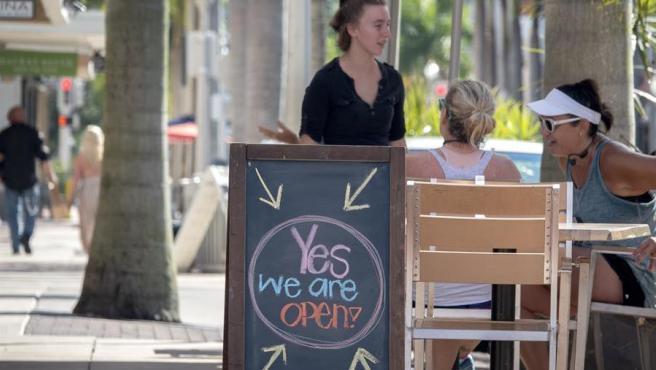 """Un cartel con el mensaje """"Sí, estamos abiertos"""", en una terraza de Fort Myers, Florida (EE UU)."""