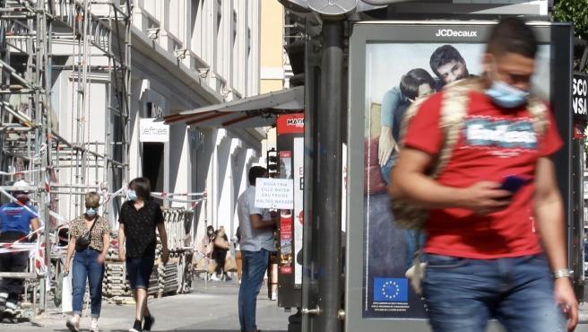 Un hombre con mascarilla consultando el móvil por la calle.