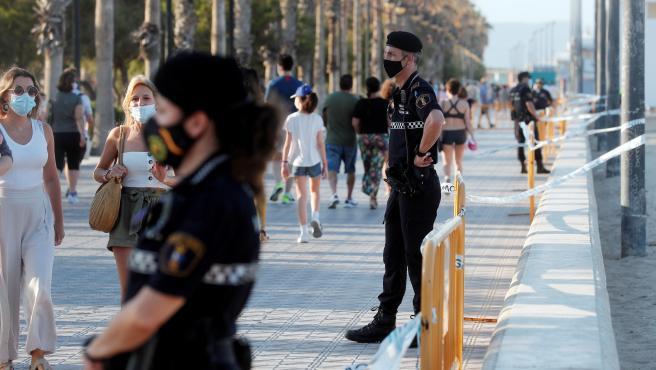 Agentes de la Policía Local de Valencia vigilan el acceso a la playa de la Malvarrosa en la pasada noche de San Juan.