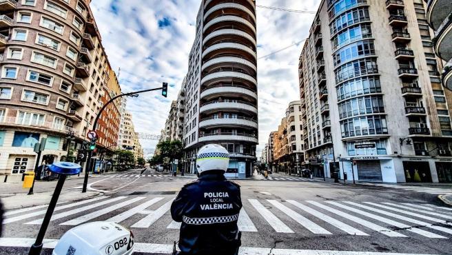 Un agente de la Policía Local de València, ante las calles vacías de la ciudad.