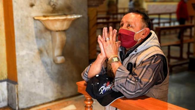 Un hombre con mascarilla por el coronavirus reza en la iglesia de Santo Domingo, en Quito (Ecuador).