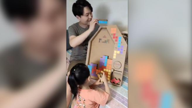 Una niña jugando al 'Tetris' casero de cartón que le ha hecho su padre.