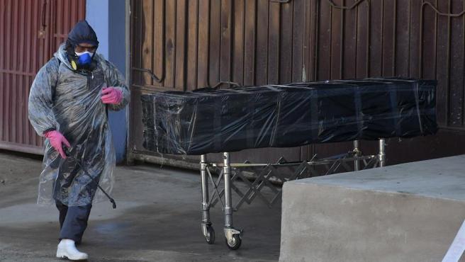 Empleados de una funeraria retiran el cuerpo sin vida de un hombre fallecido al parecer por coronavirus, que permaneció durante horas abandonado en una calle de Cochabamba (Bolivia).