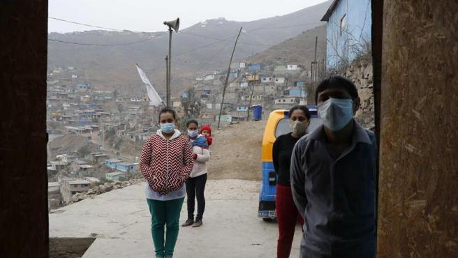 Varias personas esperan en un cerro de Lima sus raciones de una de las ollas comunes puestas en marcha a través de una red de donaciones organizada por el sacerdote español José Luis Calvo, para ayudar a la población más vulnerable afectada por la pandemia del coronavirus en la capital peruana.