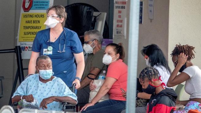 Varias personas con mascarillas por el coronavirus esperan en la puerta de un hospital en Florida, EE UU.