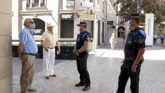 Agentes de la Guardia Urbana de Lleida recuerdan la importancia de llevar mascarilla.