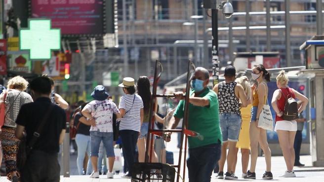 Un grupo de viandantes se protegen con mascarillas por las calles del centro de Madrid.