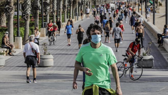 Un home amb mascarilla en la platja de la Malvarrosa a València