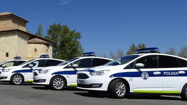 Varios coches policiales aparcados.