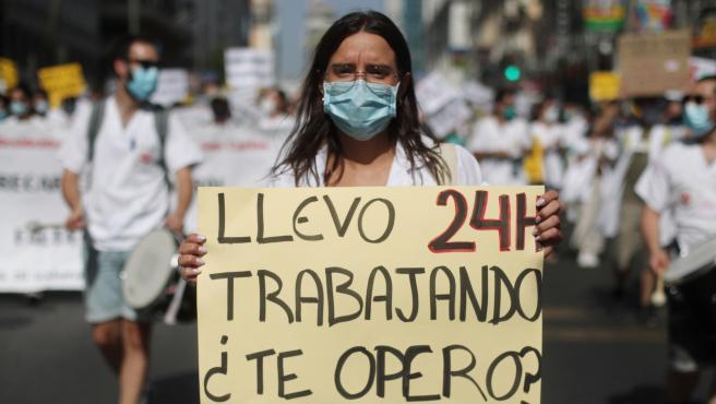 Una mujer sujeta una pancarta en la que se lee 'Llevo 24h trabajando, ¿te opero?' durante una manifestación de los médicos internos residentes (MIR) en Madrid (España)
