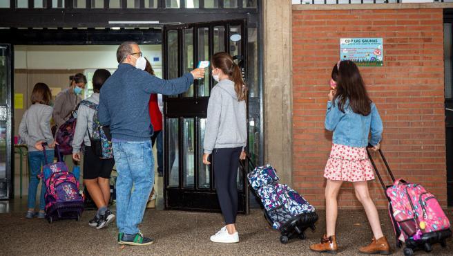 Un profesor toma la temperatura a la entrada del colegio.