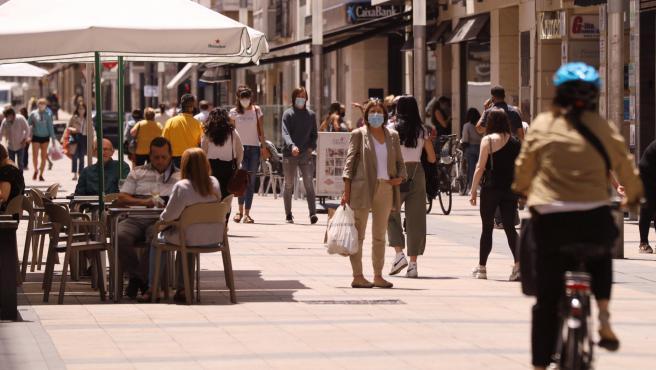 Personas paseando con mascarillas y sentadas en terrazas en una céntrica calle de Vitoria-Gasteiz.