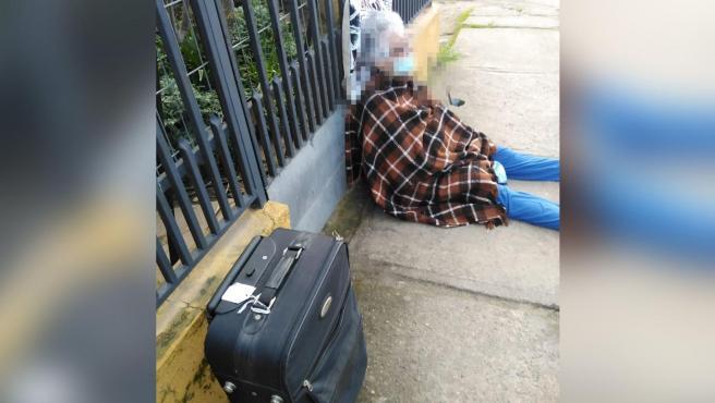 La mujer abandonada con una manta y una maleta