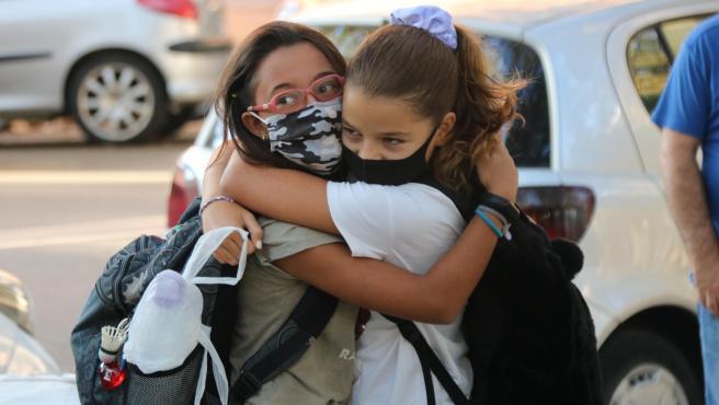 Dos niñas se abrazan en la entrada de la Escuela Catalònia de Barcelona en el primer día de clase.
