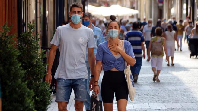 Dos jóvenes caminan con mascarilla por una calle de Reus (Tarragona), el 18 de agosto de 2020.