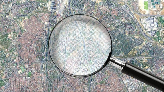 Imagen de recurso de una lupa sobre un mapa de Madrid.