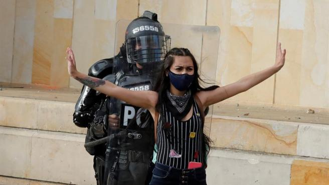 Una manifestante defiende a agentes policiales durante una protesta contra el Gobierno en Bogotá, Colombia.