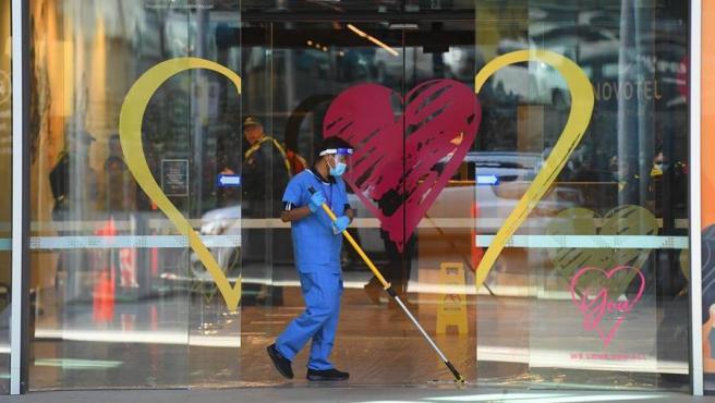 Un trabajador con material de protección por la pandemia del coronavirus limpia la entrada de un hotel en Melbourne, Australia.