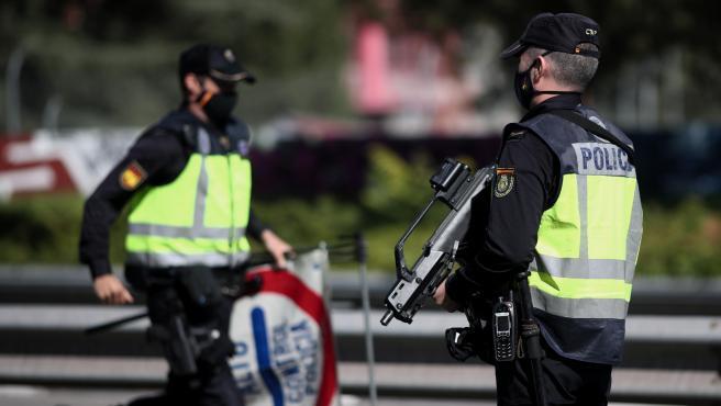 Dos agentes de la Policía Nacional durante un control policial de movilidad en Madrid.