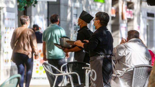 Dos camareros trabajan en una de las terrazas ubicadas en el Paseo del Prado, vía peatonalizada durante este fin de semana, en Madrid