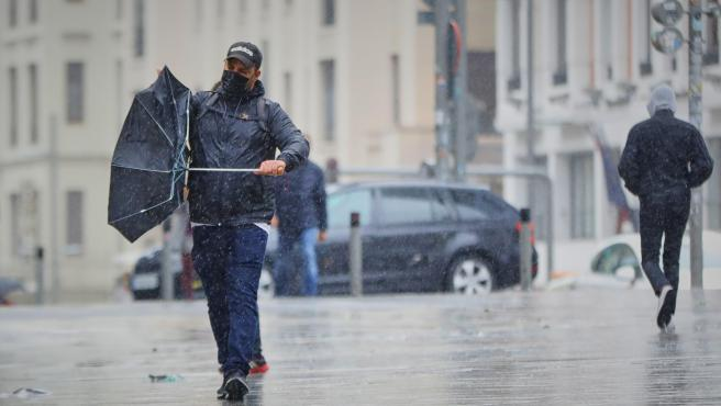 Un hombre camina bajo la lluvia en Madrid.