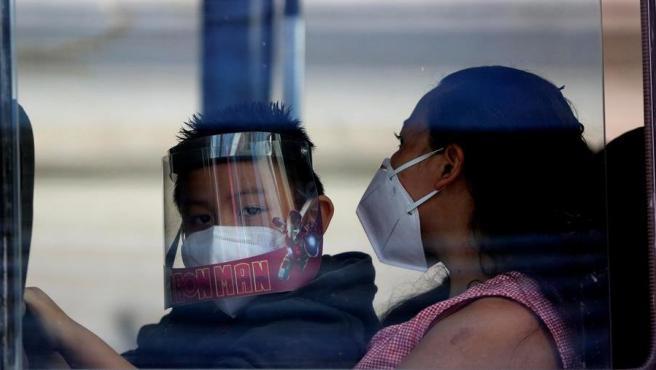 Un niño y su madre, ambos con mascarillas por el coronavirus, en un autobús urbano de Tegucigalpa, Honduras.