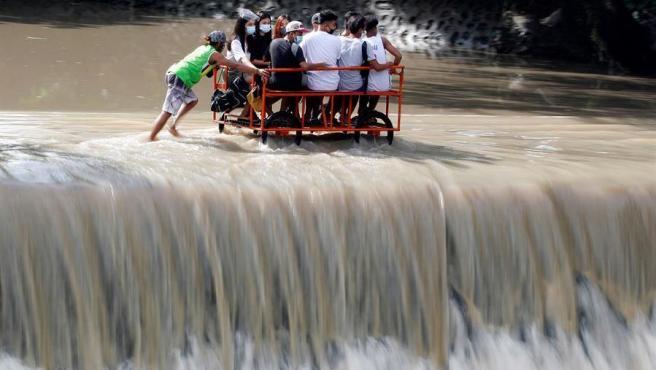 Varias personas cruzan en una carreta una presa desbordada en la frontera entre la provincia de Cavite y la ciudad de Las Piñas, en Filipinas, antes de la llegada del tifón Molave.