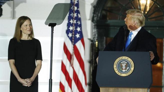 Amy Coney Barrett, durante la ceremonia de toma de posesión de su cargo como nueva jueza del Tribunal Supremo de EE UU, junto al presidente estadounidense, Donald Trump, en la Casa Blanca.