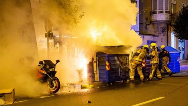 Bomberos apagan un contenedor ardiendo en Logroño durante los disturbios registrados en las protestas contra las restricciones impuestas para frenar el avance del coronavirus.