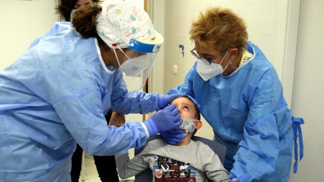 Dos enfermeras hacen el test rápido de antígenos a un niño.