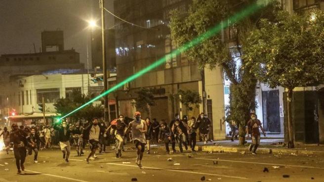 Policías y manifestantes se enfrentan en Lima, Perú, durante una protesta contra el gobierno de transición de Manuel Merino.