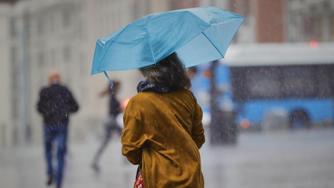 Una persona camina en Madrid durante una jornada de lluvias y fuertes vientos.