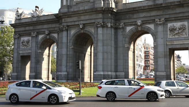 Imagen de recurso de varios taxis a su paso por la Puerta de Alcalá, en la ciudad de Madrid.