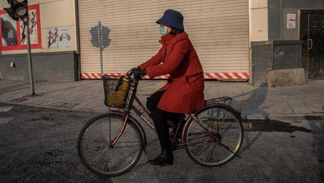 Una mujer con mascarilla por el coronavirus circula en bicicleta por una calle de Pekín, China.