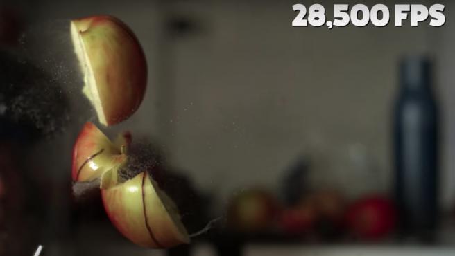 Una manzana explotando en el aire a cámara lenta.