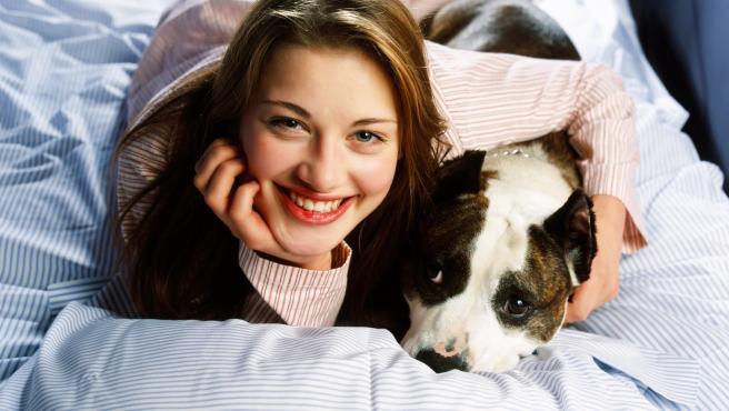 Una mujer abraza a su perro.