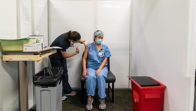 La enfermera Mackenzie Bochtler administra la vacuna contra la Covid de Pfizer-BioNTech a su compañera Michelle Kimura en la clínica de vacunación de un centro médico de la Universidad de Washington, en Seattle.