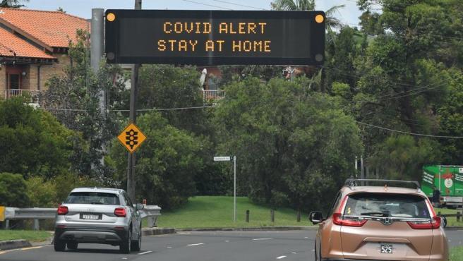 Una señal llama a la población a quedarse en casa por una alerta de COVID-19, en una carretera de Sídney, Australia.