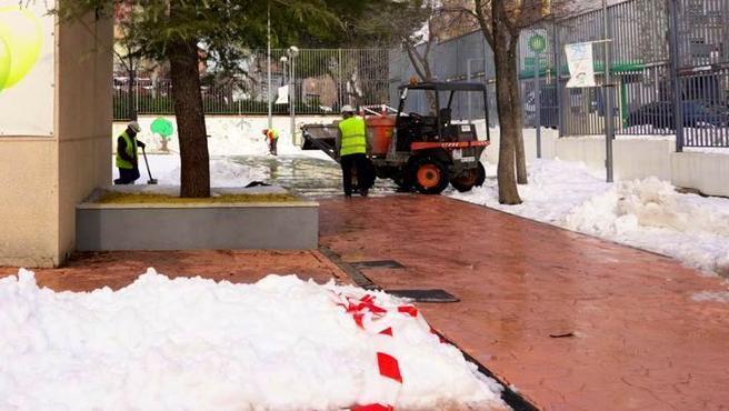 Unos operarios limpian el acceso a un colegio de Madrid.