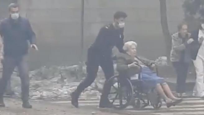 Una anciana es evacuada de la residencia afectada por la explosión.