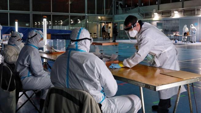 Personal de la mesa electoral limpia el espacio habilitado para la votación de personas positivas COVID.