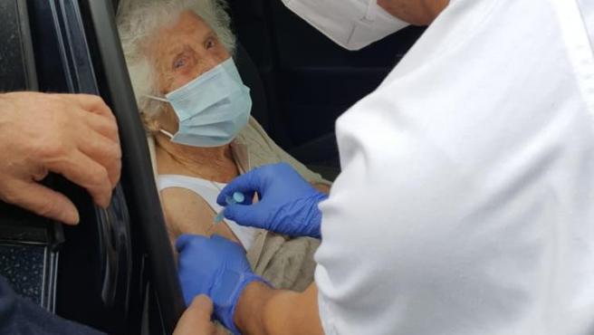 Un sanitario vacuna este martes contra la Covid a una mujer de 101 años sentada en un coche en Canet de Mar (Barcelona).