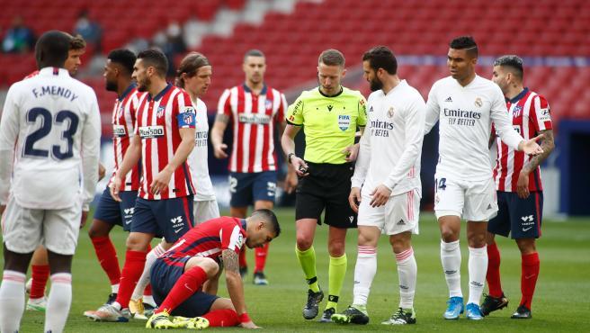Jugadores del Atlético y Real Madrid, con el árbitro Hernández Hernández en el centro