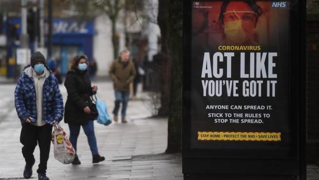 """Un cartel del sistema público de salud británico sobre el coronavirus, con el mensaje """"Actúa como si lo tuvieses, cualquiera puede transmitirlo"""", en Londres."""