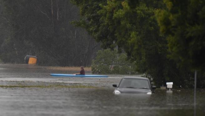 Una persona navega en un kayak en una carretera inundada al noroeste de Sídney, en Nueva Gales del Sur, Australia.