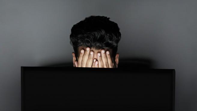 Un joven delante de una pantalla de un ordenador.