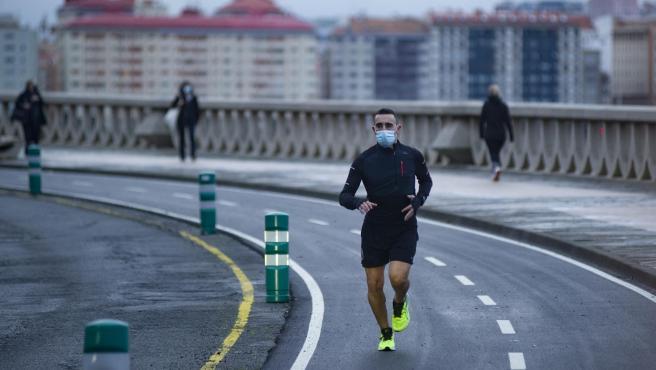 Una persona corre en solitario y con mascarilla en A Coruña.
